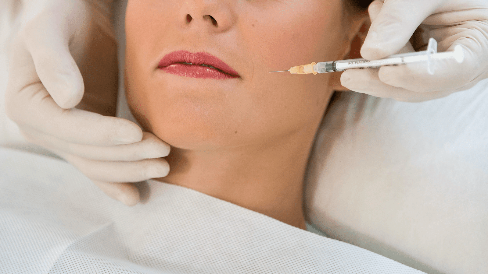 A woman with red lips gets a botox injection in her cheek.