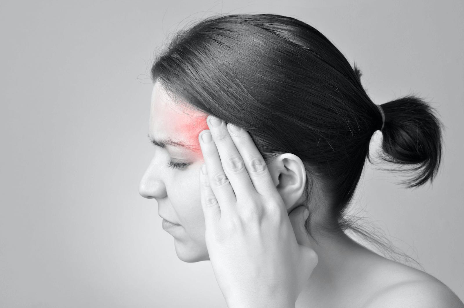 A black and white picture highlighting a woman's throbbing headache.
