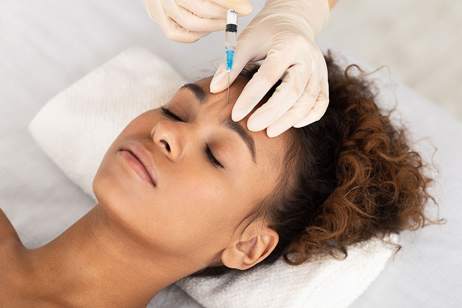 A young woman lays on a white towel and receives botox injections.