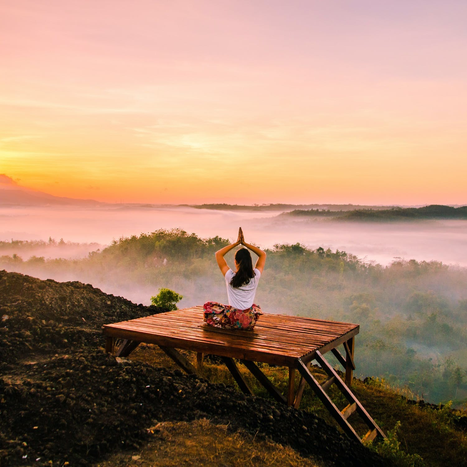 A woman practices yoga on a deck in front of a foggy landscape.