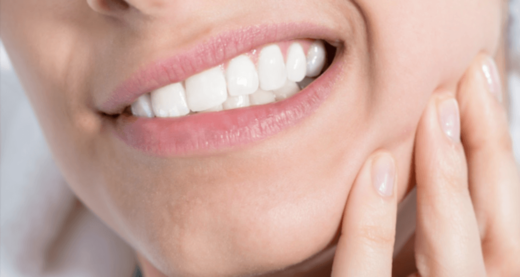 A close-up picture of someone clenching their teeth.