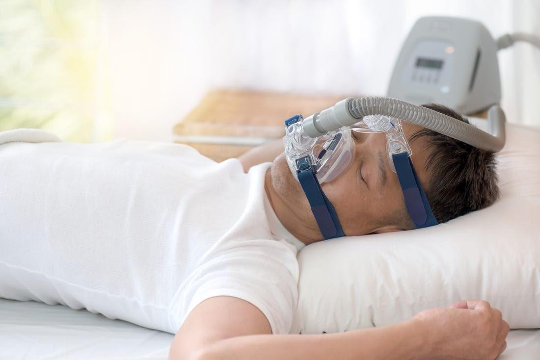 A man in a white shirt uses a CPAP machine for sleep apnea.