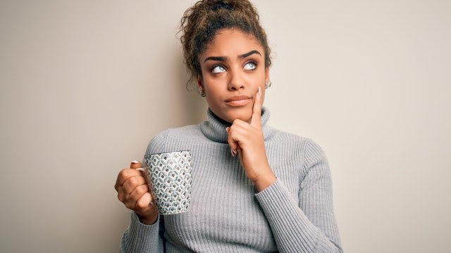 A woman in a gray turtleneck drinking coffee and thinking about sleep apnea.