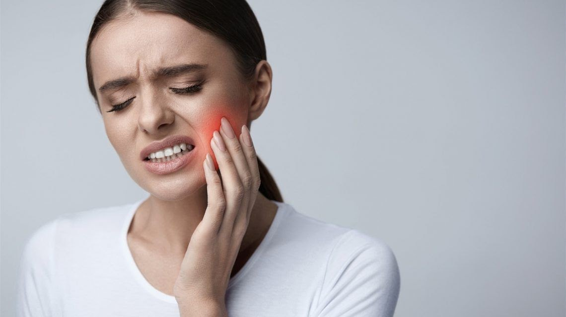 A woman presses on her cheek due to tooth pain.