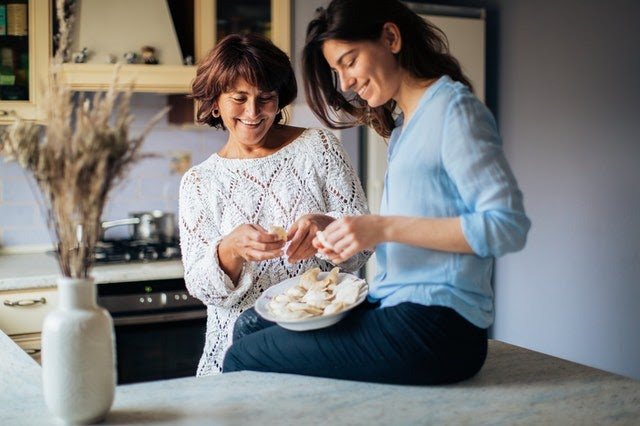 Two happy women bake healthy holiday treats together.