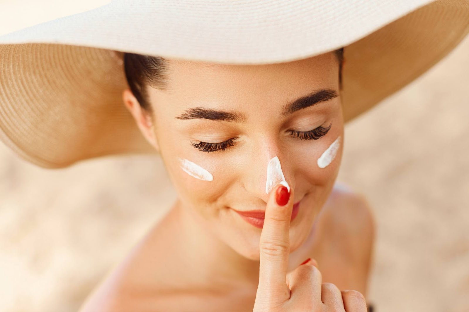 A young woman wearing a sun hat applies sunscreen.