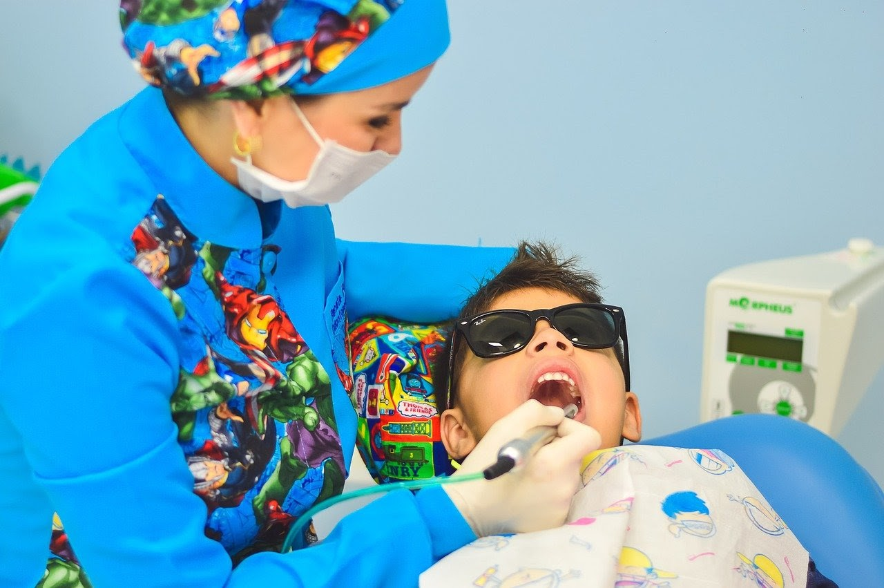 a child gets his teeth cleaned by his dentist