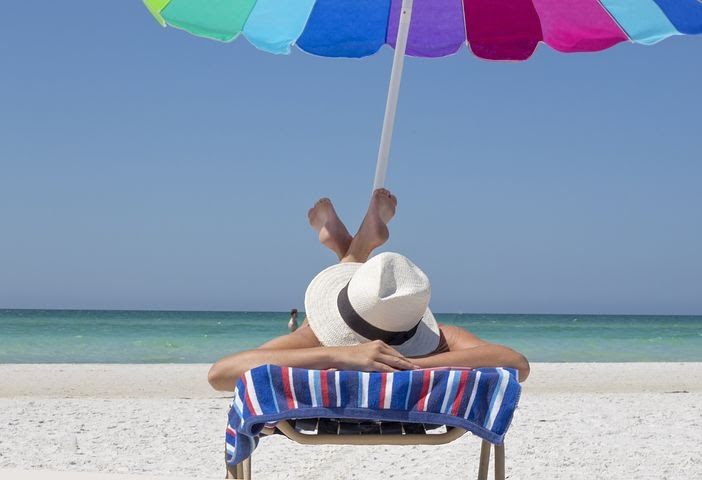 a woman relaxes in the sun wearing a sun hat and using an umbrella