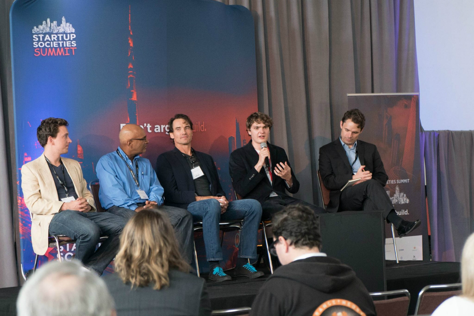 Thibault Serlet speaking in San Francisco during the Special Economic Zones Panel with Tom W Bell, Mark Lutter, Michael Castle Miller, and Park Muelle Zone Manager