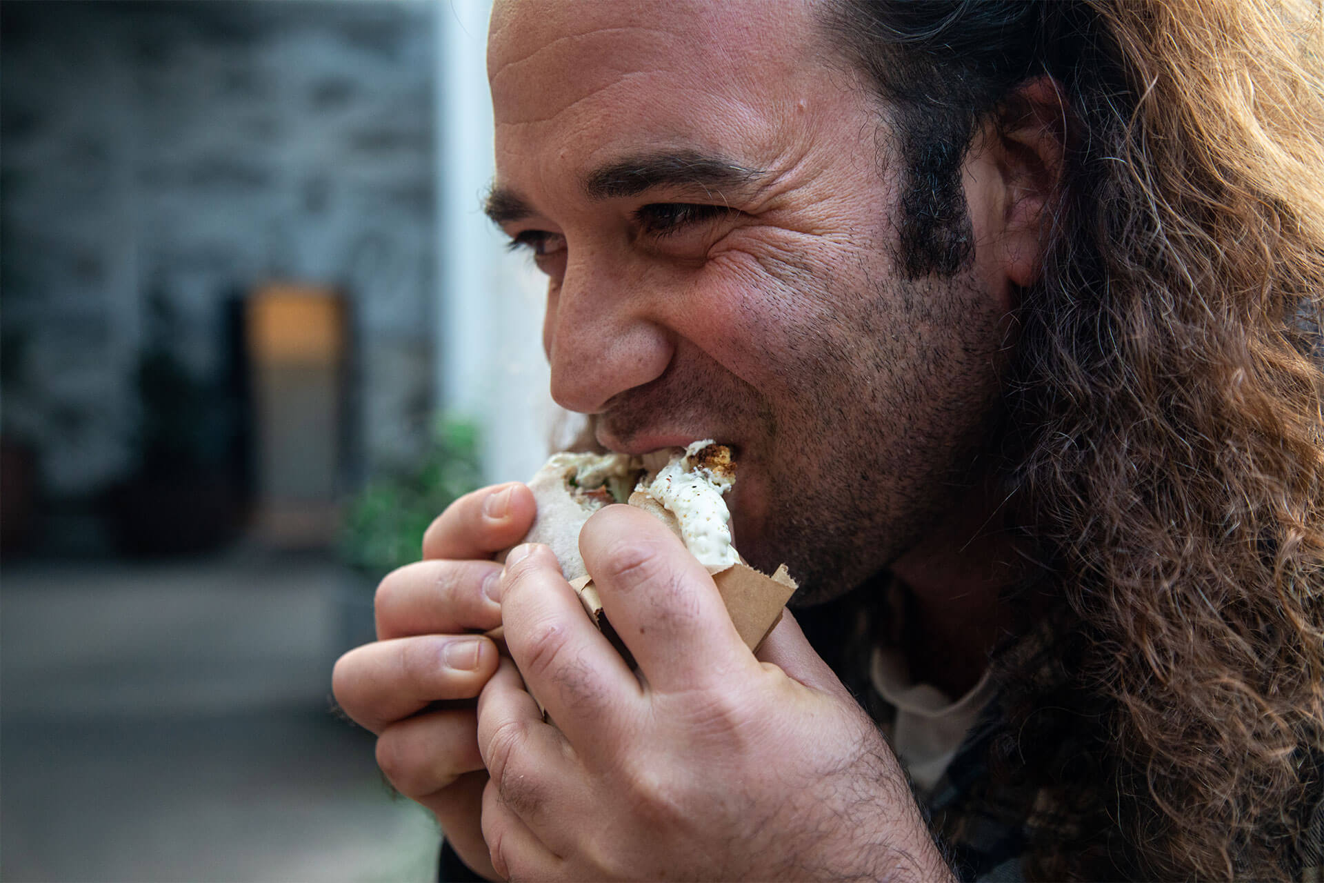 A guy eats Carmel's pita