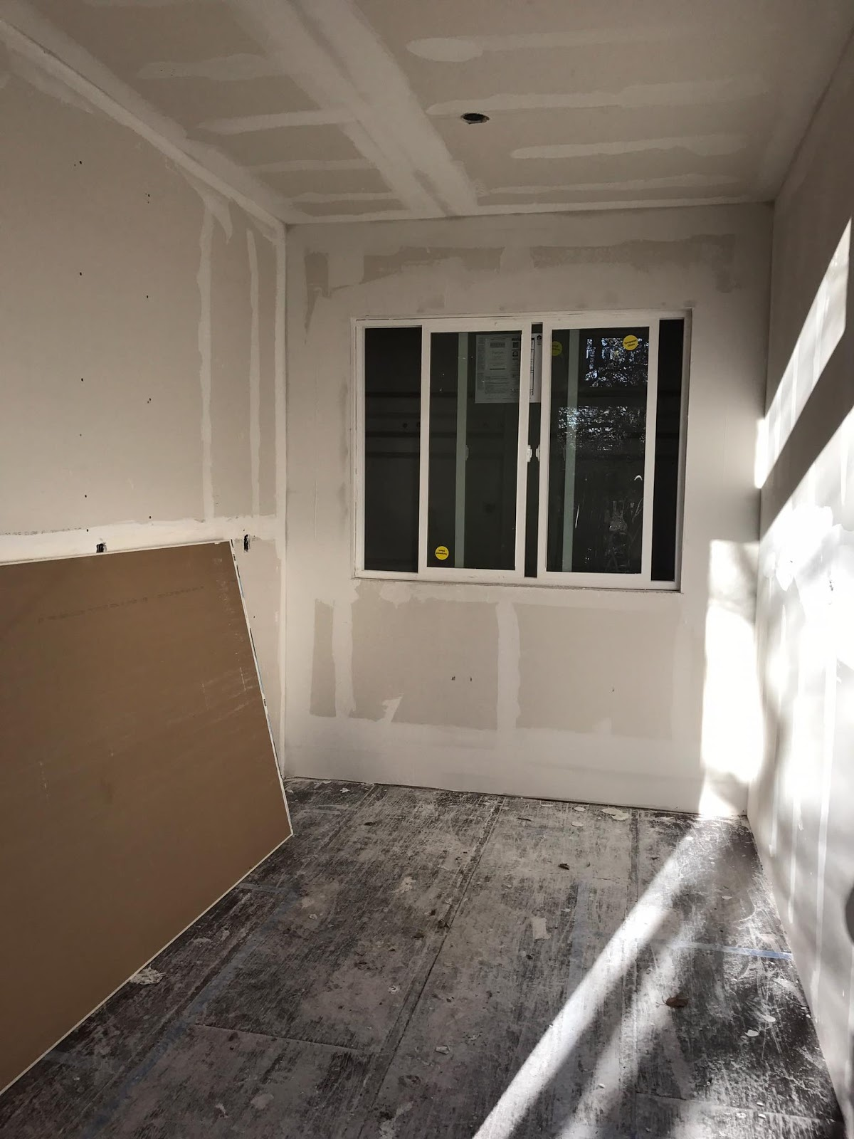 raw drywall with a new storm window built into a shipping container