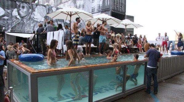 young people partying around a transparent shipping container pool