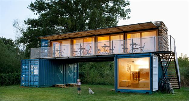 2 story home with an upstairs patio made from blue shipping containers