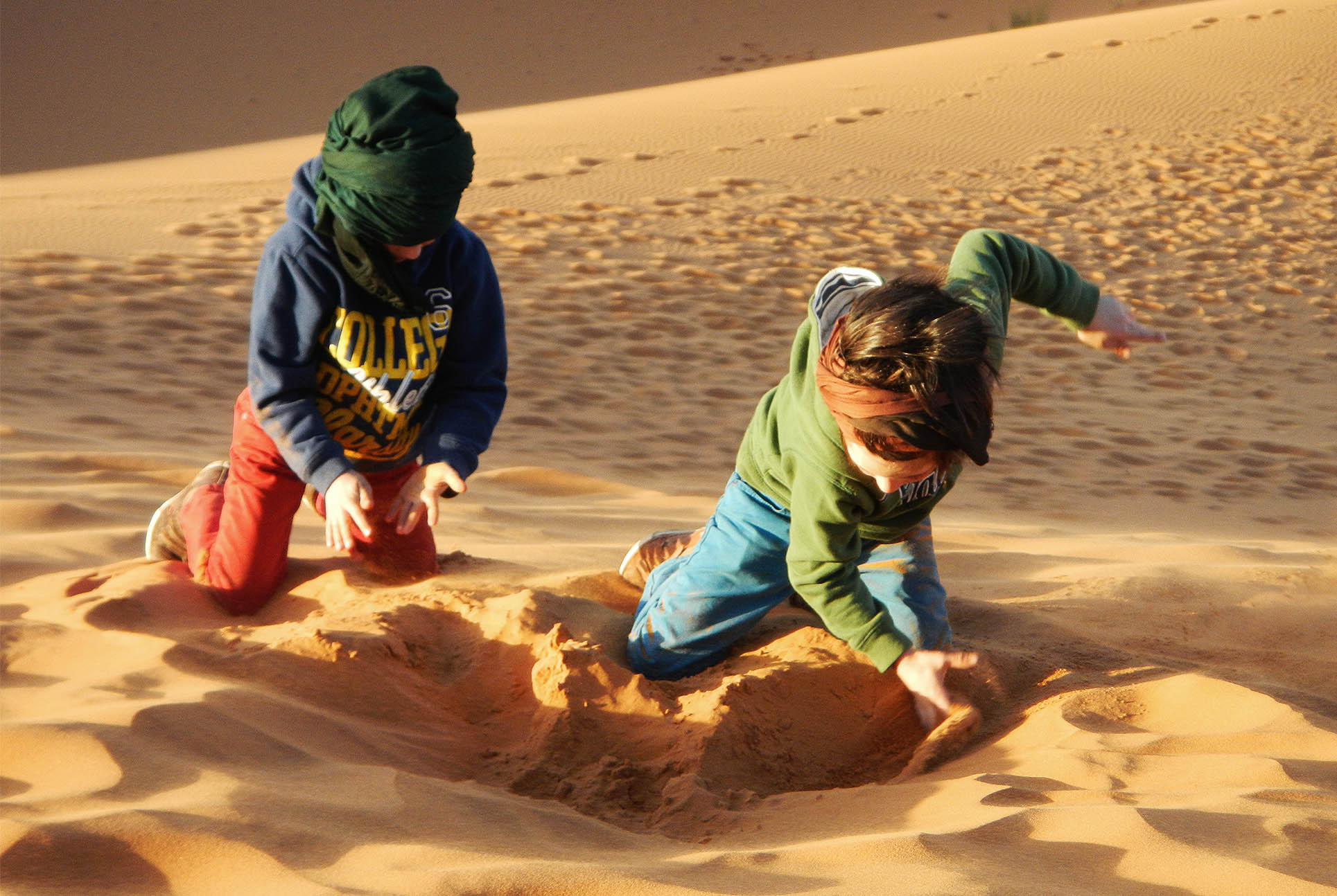 children playing in the sand dunes of moroccan desert, Morocco