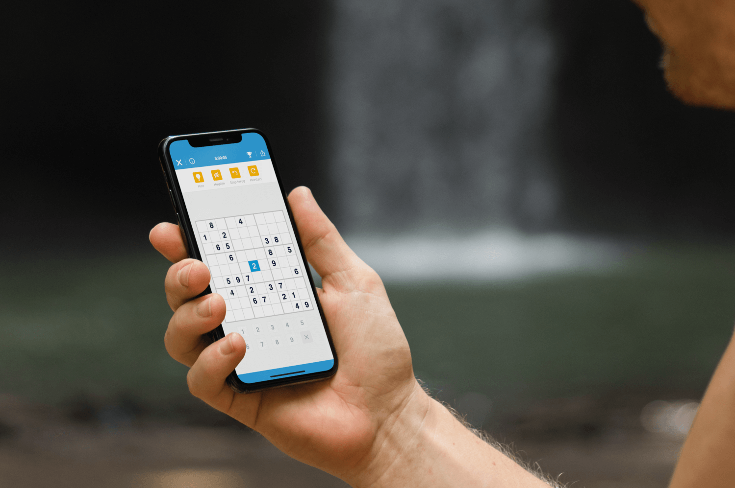 A hand holding an iPhone with Sudoku