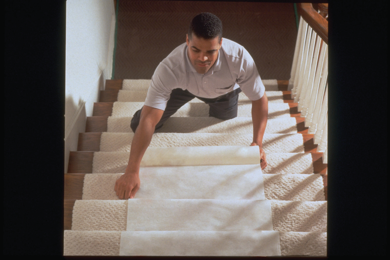 Man installing a floor runner to protect carpeting