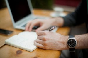 Man with wristwatch writing working