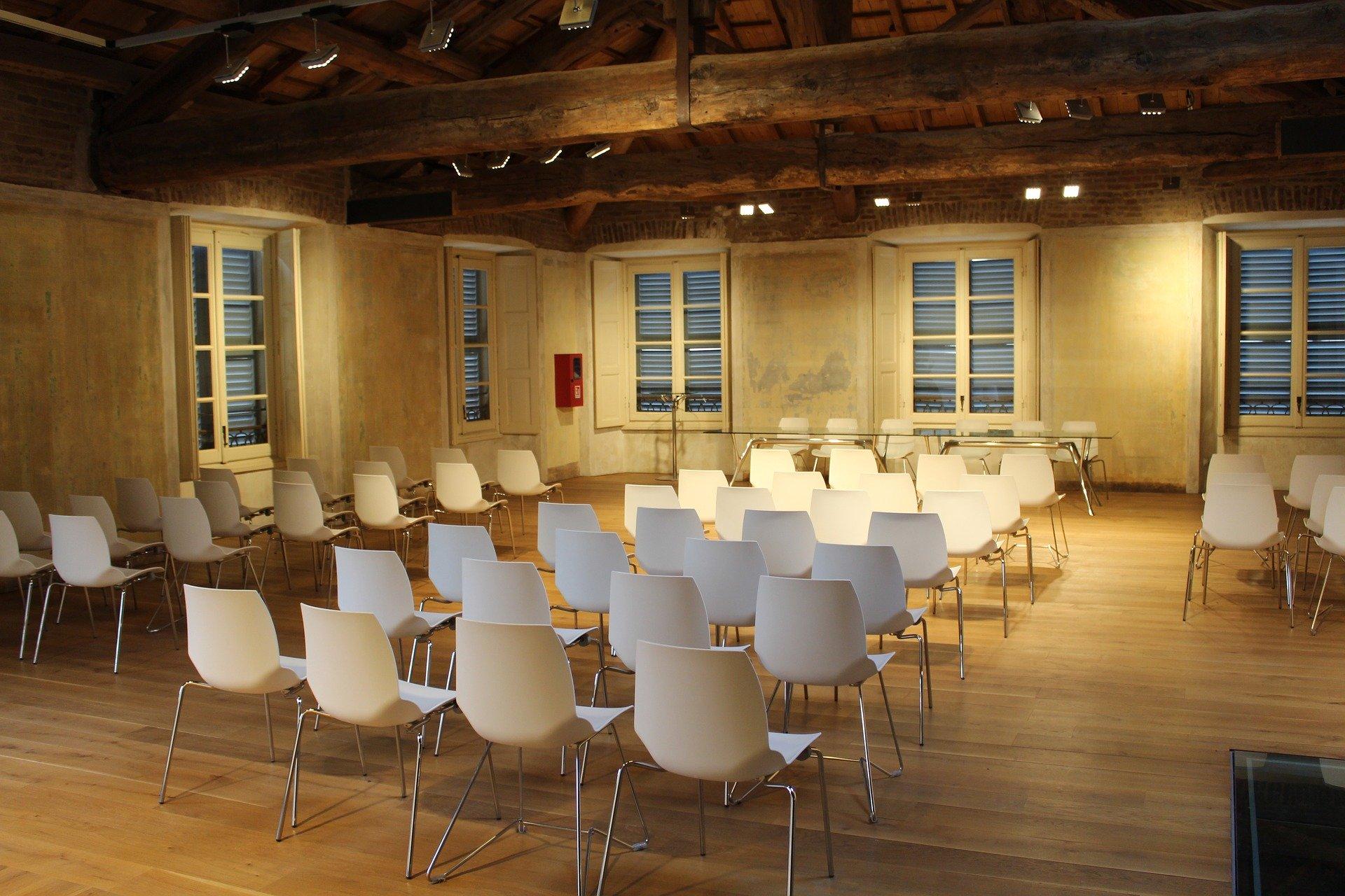 Ein Seminarraum mit weißen Stühlen und angenehmen Licht