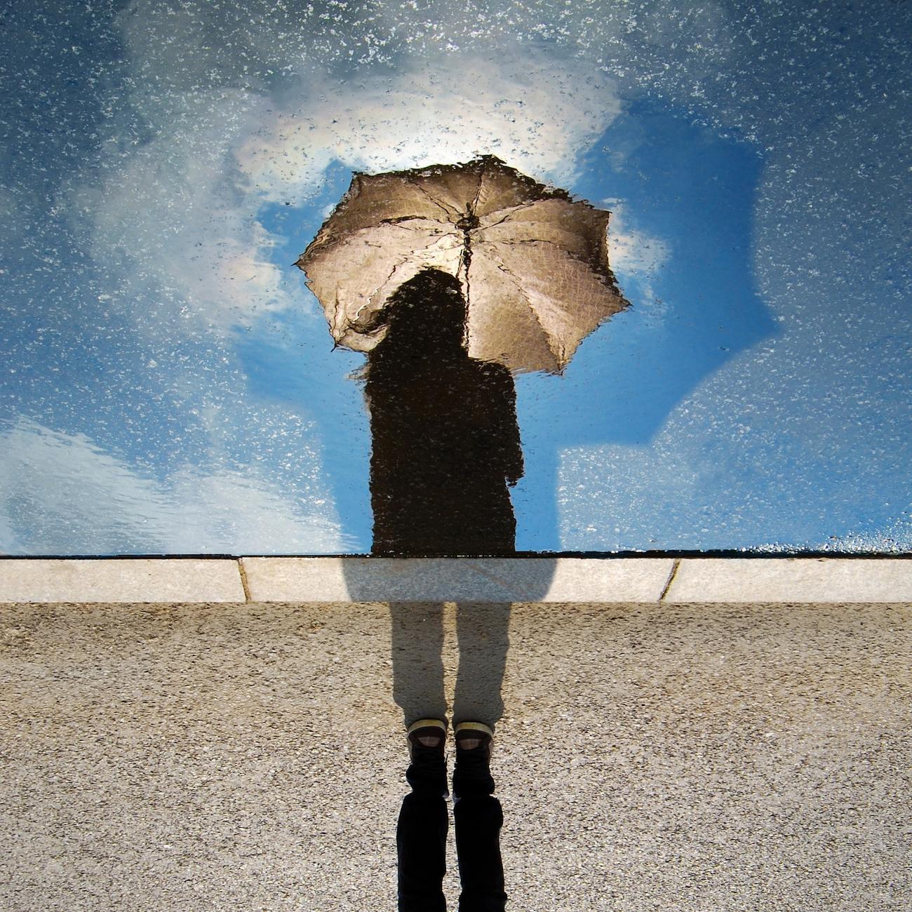 Frau mit Regenschirm vor blauem Himmel mit Wolken