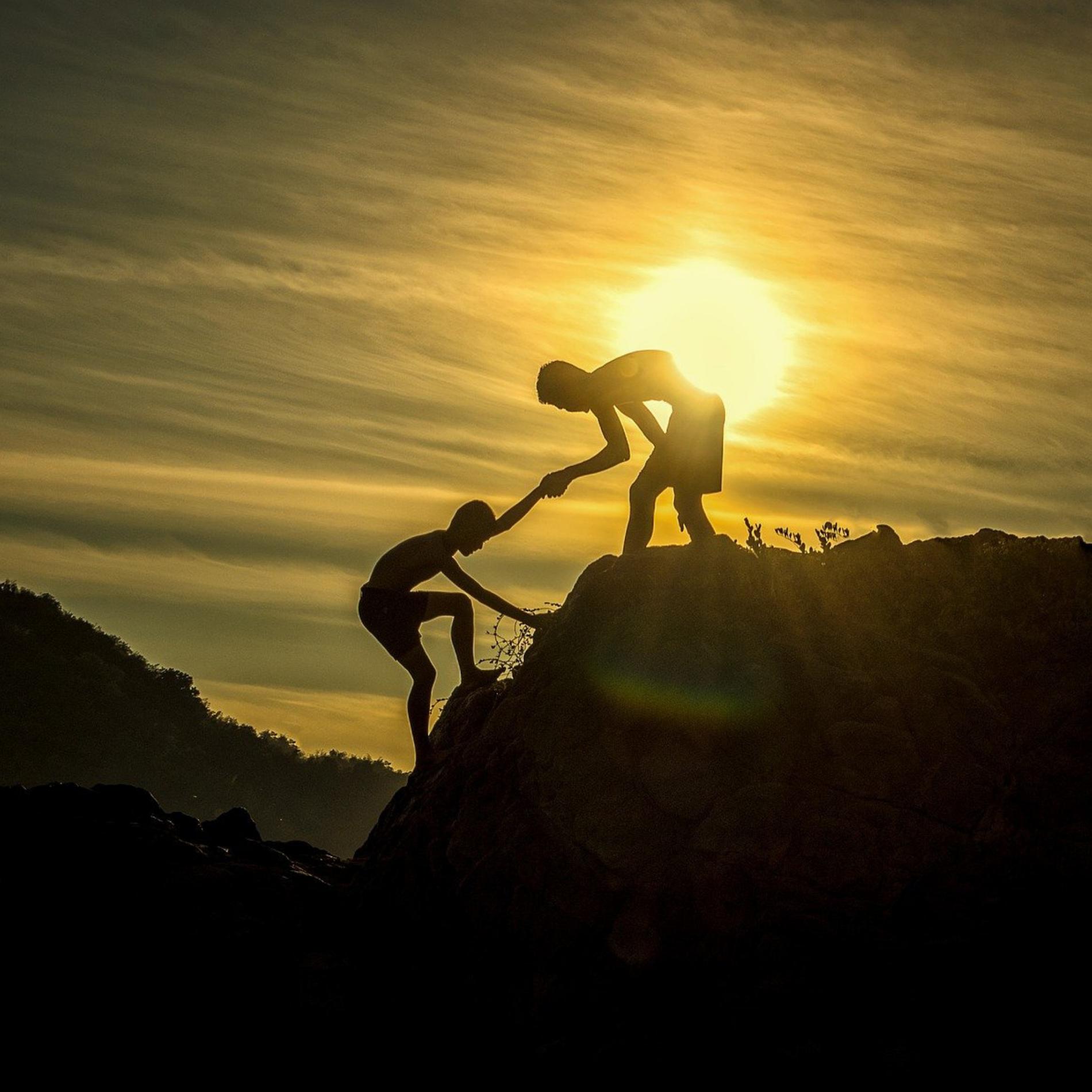zwei Wanderer auf einem Berg mit dem Sonnenuntergang in Hintergrund. Deine hilft dem anderen.