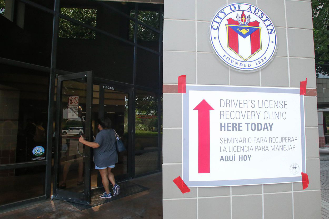 The outside of a City of Austin municipal building. A flyer promoting one of TFDP's Driver's License Recovery Clinics has been taped to an outside wall with a red arrow encouraging people to look for the clinic inside.