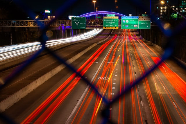 A view of a Houston highway overpass at night. Neon streaks of red and orange represent moving cars. A set of highway signs is blurred but visible through fence links.