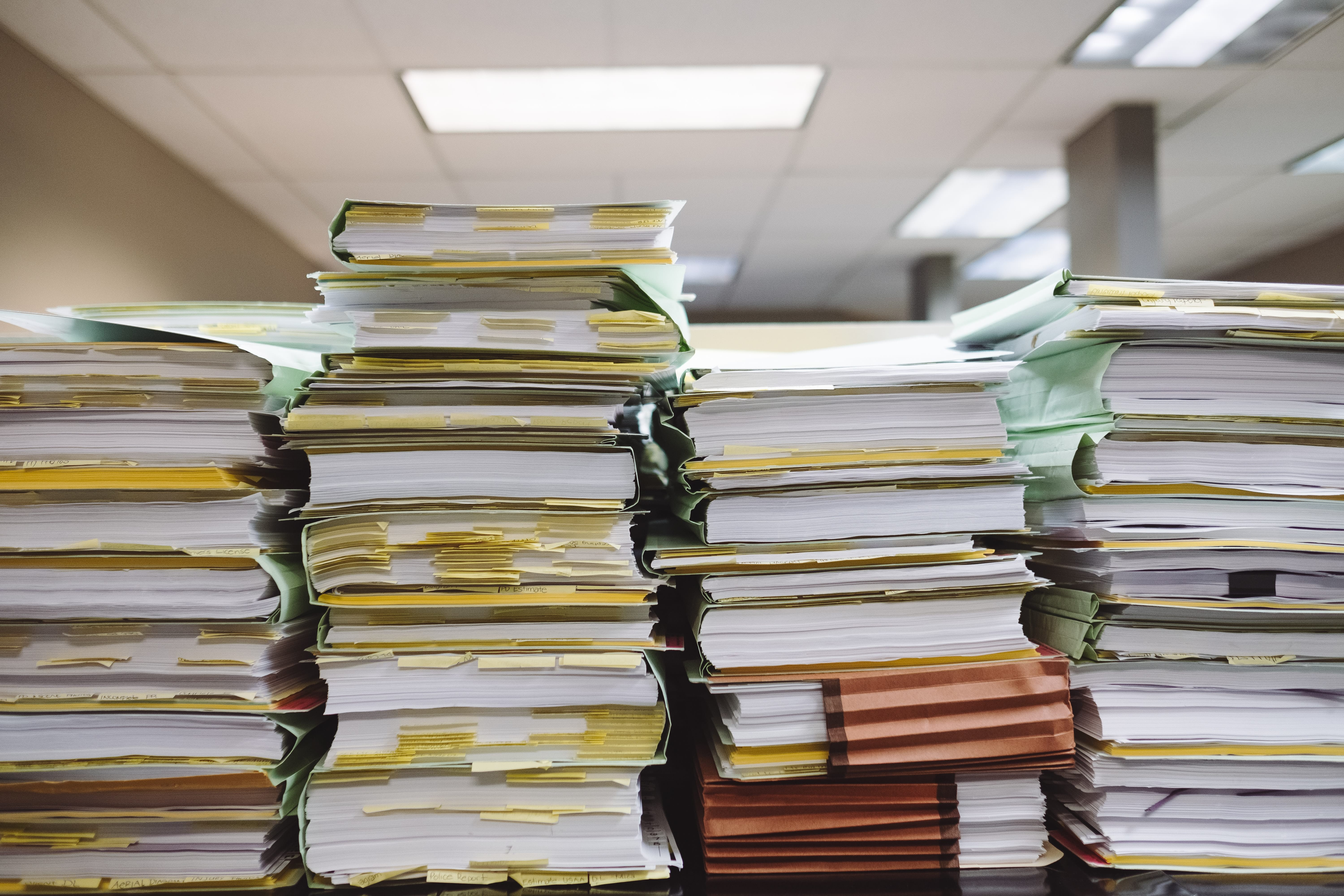 Four piles of papers are stacked on a table in a room with overhead fluorescent lighting. The papers are separated by accordion folders and paper binders.  Many pages have yellow post-its poking through them.