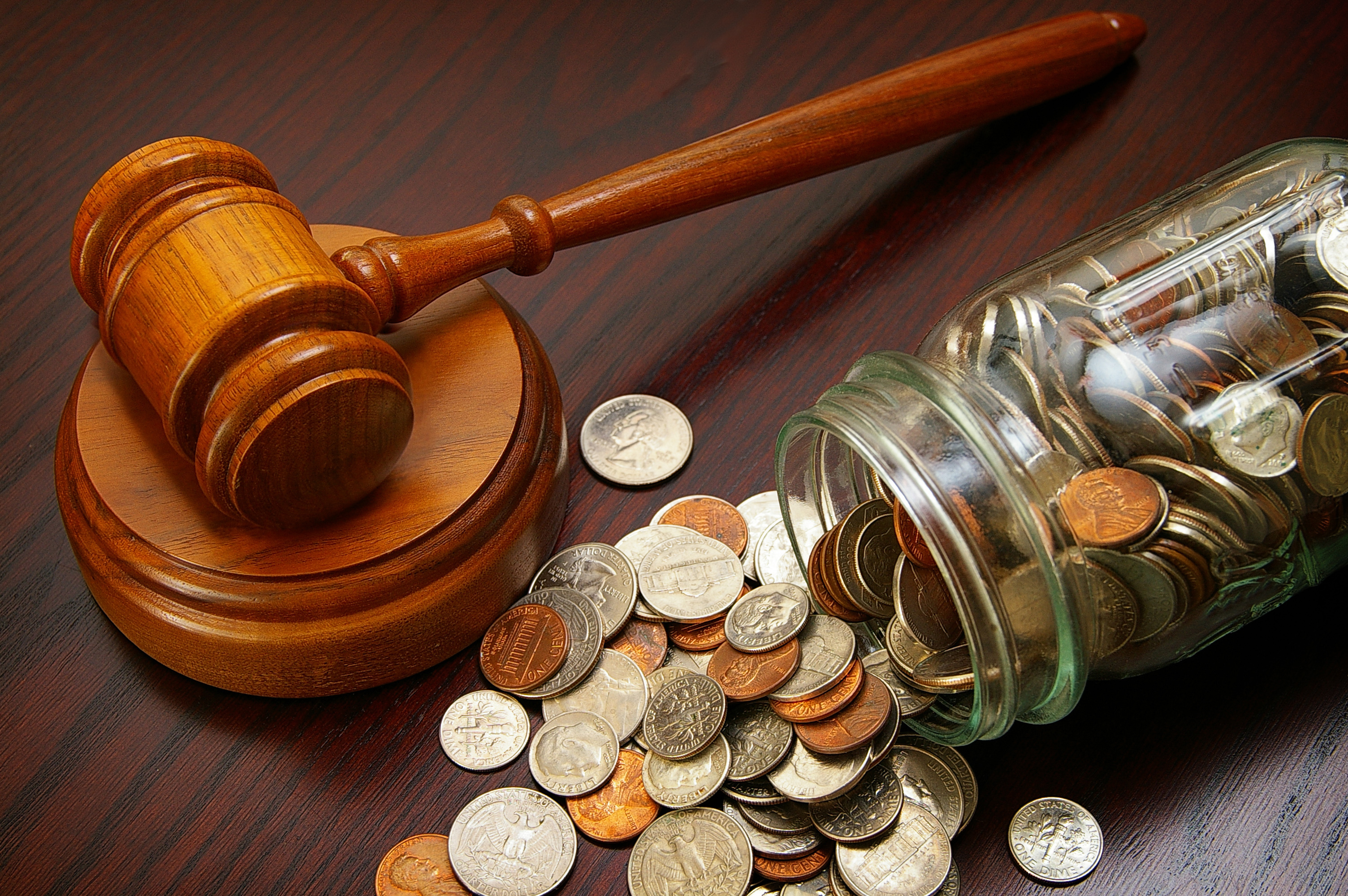 A photograph of a dark wooden gavel resting on a table. Next to it, a mason jar of American coins has tipped over and spilled onto the dark mahogany table. The coins include dimes, pennies, nickels and quarters.
