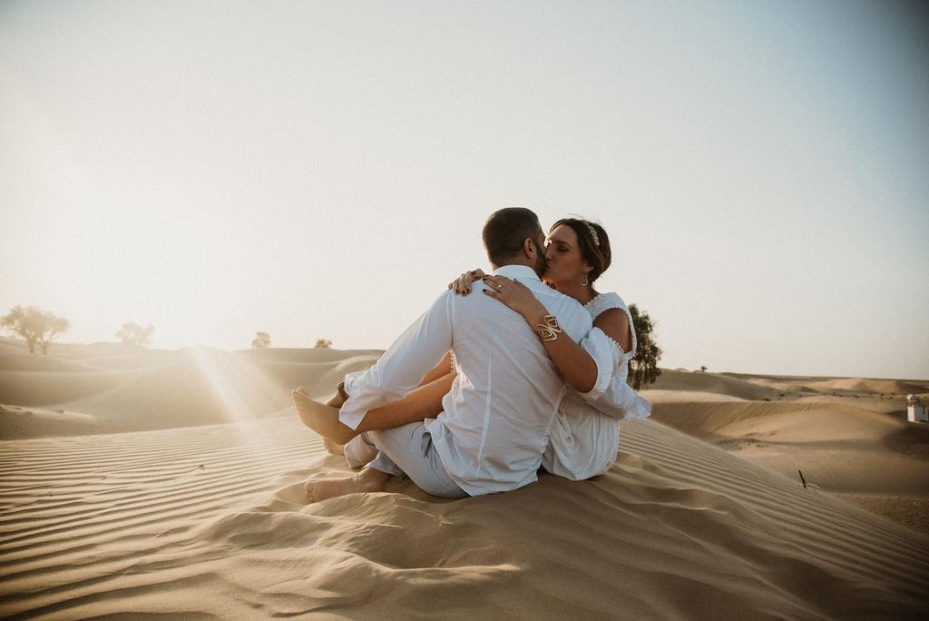 Fotoshooting in der Wüste - Küssendes Paar auf einer Düne
