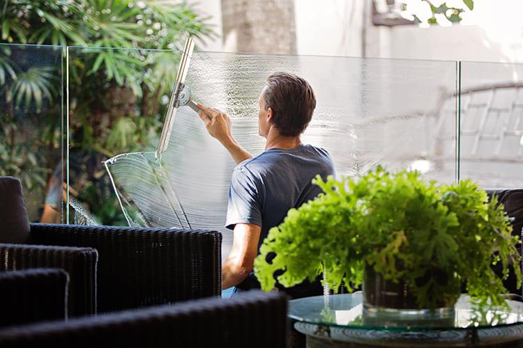 Mann putzt Fensterscheibe