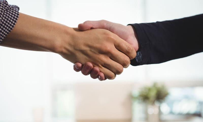 Haus verkaufen:Käufer und Verkäufer unterschreiben den Vertrag auf dem Notariat.