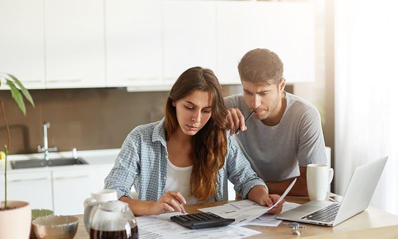 Erneuerungsfonds im Stockwerkeigentum:Mann und Frau rechnen in der Küche