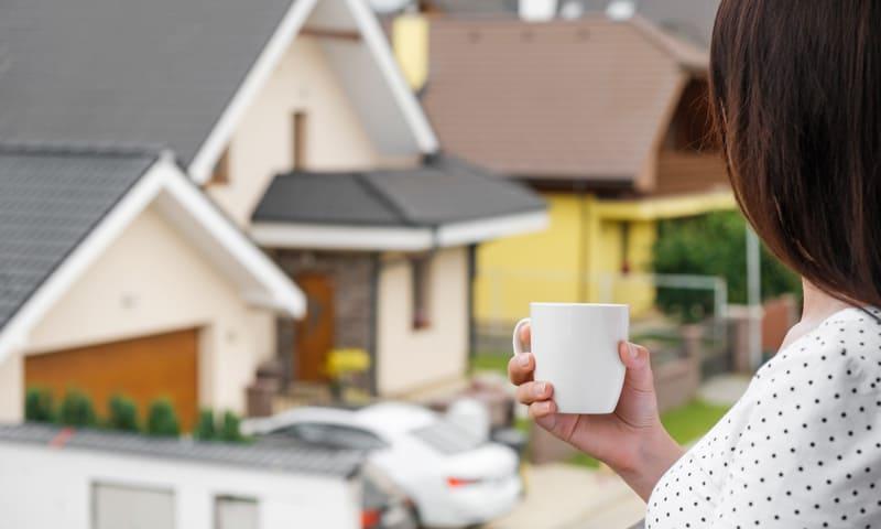 Frau schaut aus Balkon in Nachbarschaft mit Häusern