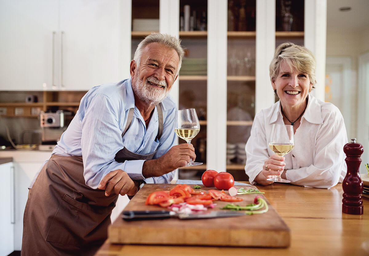 A man and woman having some wine after preparing food.
