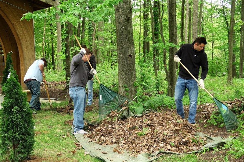 C2 Team members raking IKUS grounds during service project