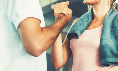 A handshake between two people illustrating that an accountability partner or personal trainer helps make exercise a habit