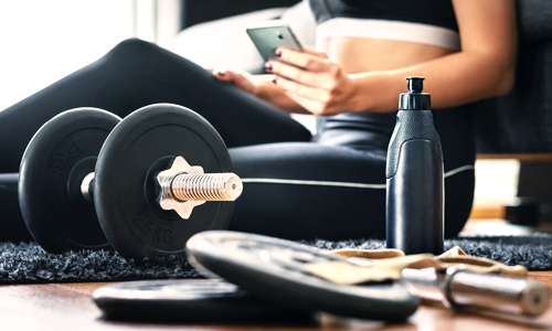 A woman sitting on the her living room floor with dumbbells getting ready to follow a convenient workout on her phone