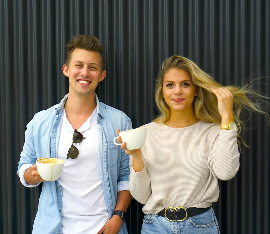 Man and woman smiling drinking coffee