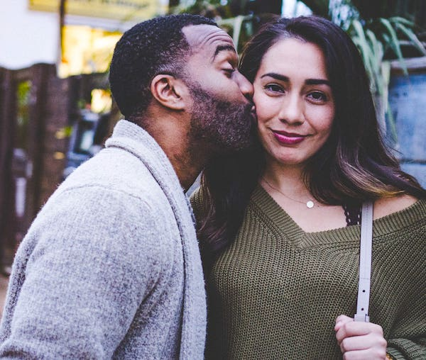 Man kissing smiling woman on cheek