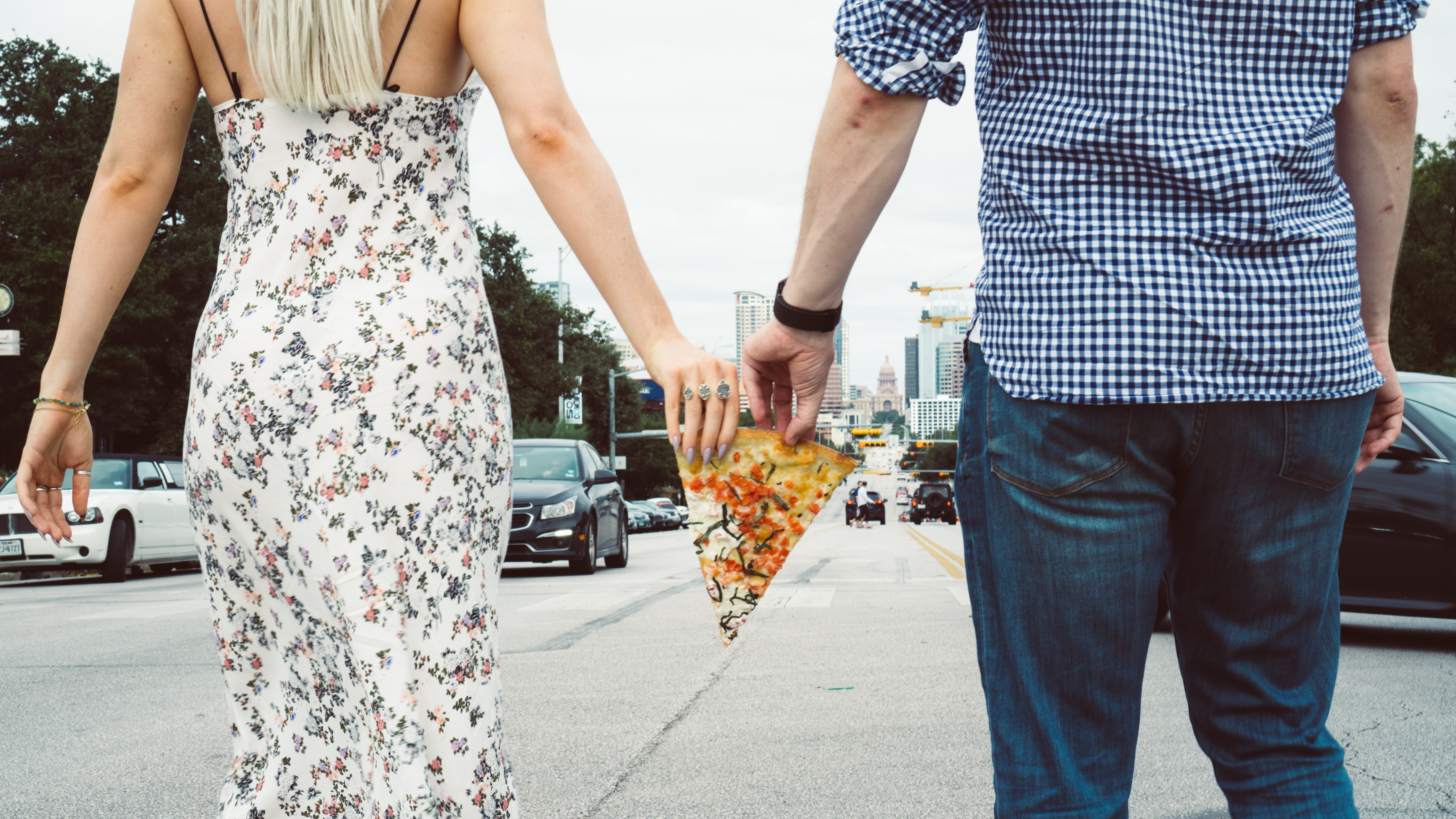 Man and woman holding pizza between their hands