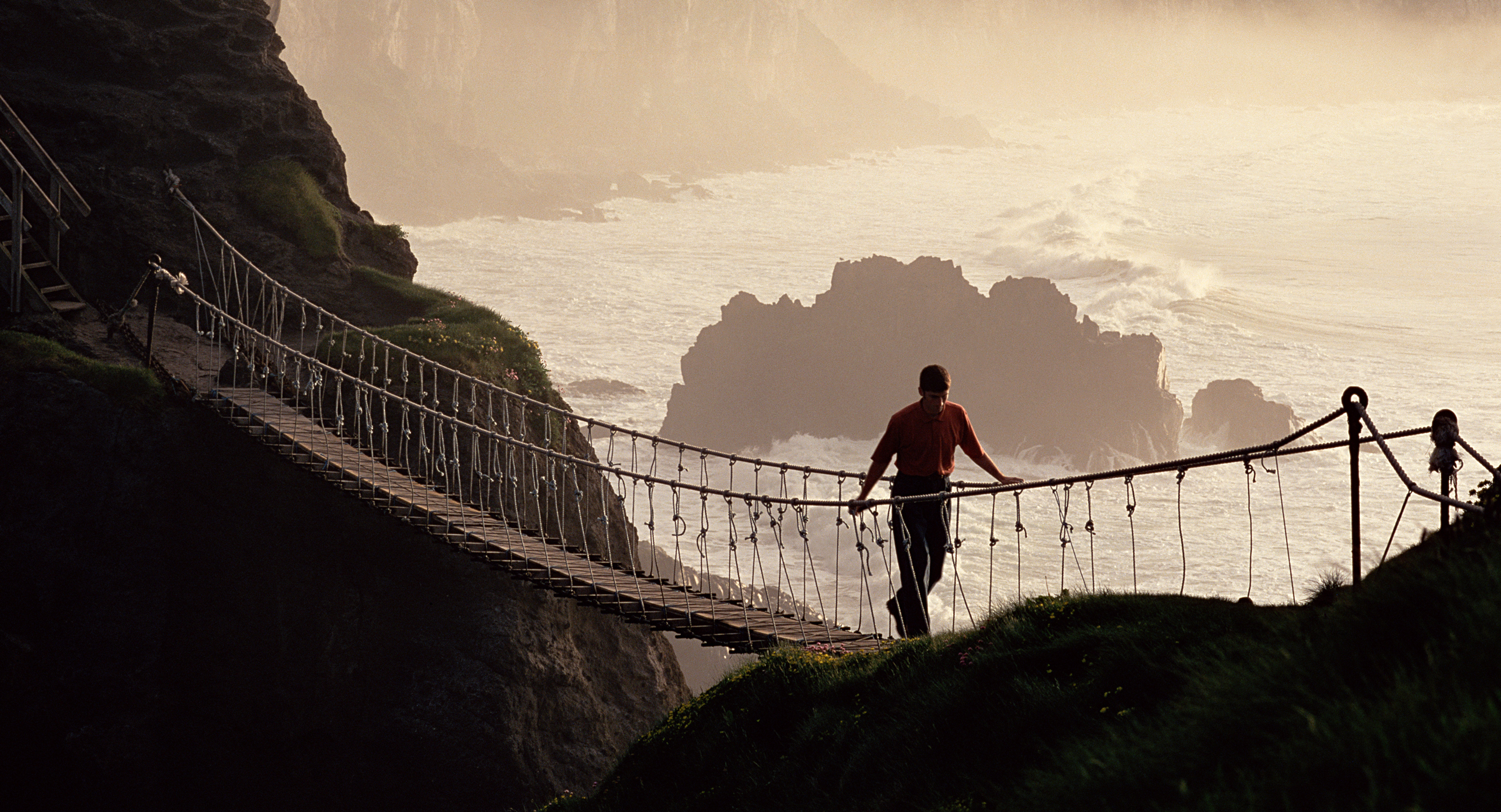 An Essential Ireland guest crosses the Carrick-a-rede rope bridge on one of our True North Tours