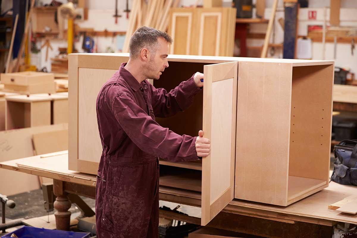 Carpenter using screwdriver to make fine adjustments to cabinet door hinge