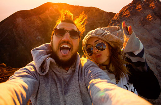 Excited man and woman selfie hiking in mountains