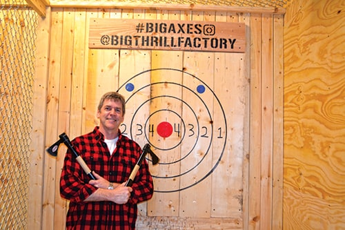 man in red flannel shirt preparing to throw axes