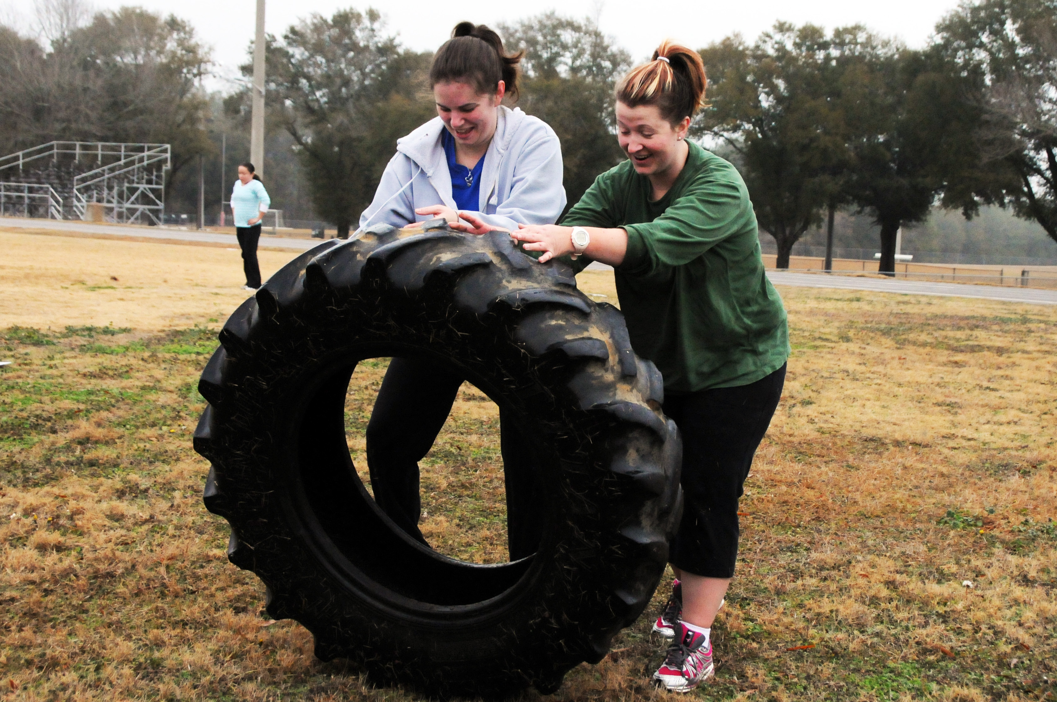 Two young women moving a big tire during a fitness boot camp.