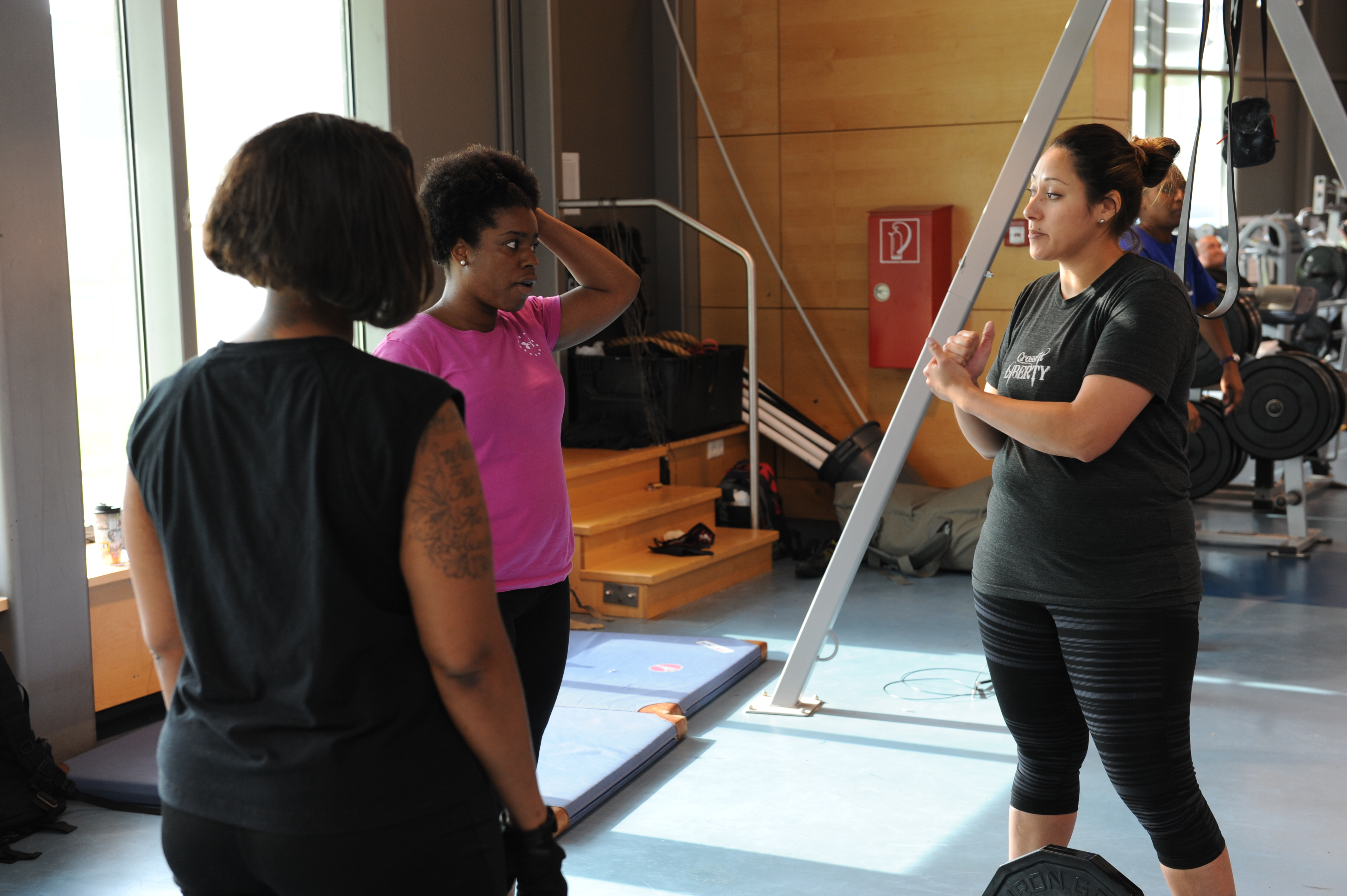 A personal trainer working with two female clients