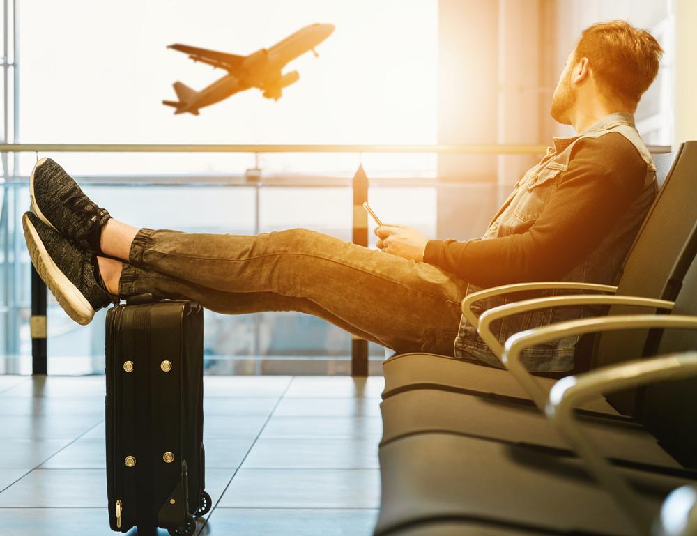 En mann som venter på flyet sitt ved gate