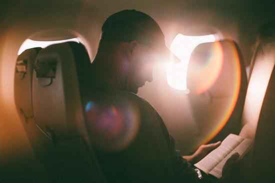 En mann sitter og leser i flysetet sitt