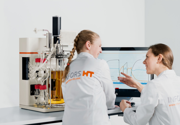 Two women in front of a tabletop bioreactor and the eve desktop software
