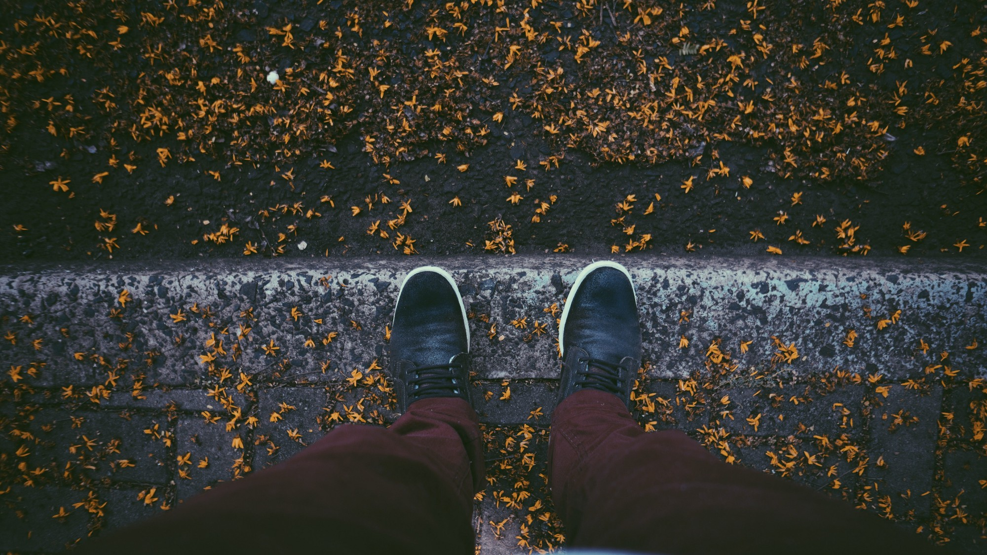 A photo of a person looking down at his shoes.